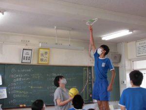 背の高い生徒が,天井に張り付けるお手伝いをしています。理科の授業中です。