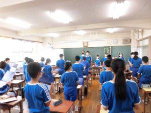 朝の会の時間。歌声委員の先輩が,1年生と一緒に校歌の練習をしています。